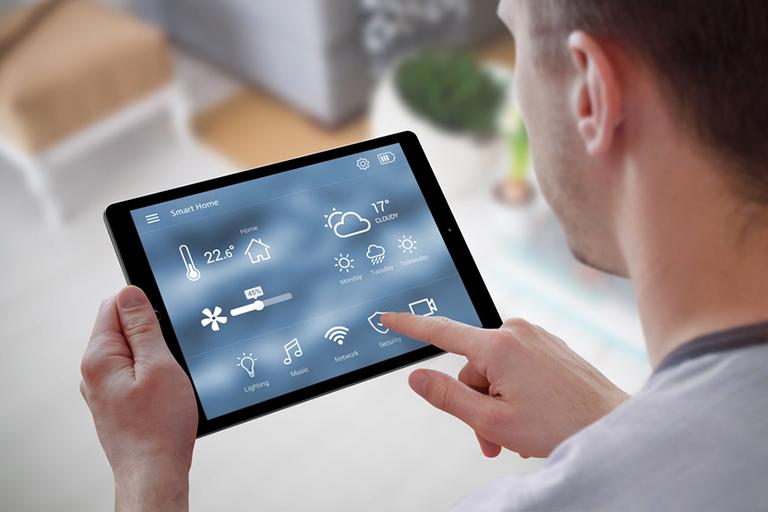 Mann konfiguriert Smart Home am Tablet